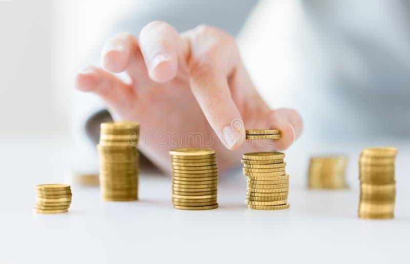 Закройте вверх женской руки кладя монетки в столбцы стоковое фото rf