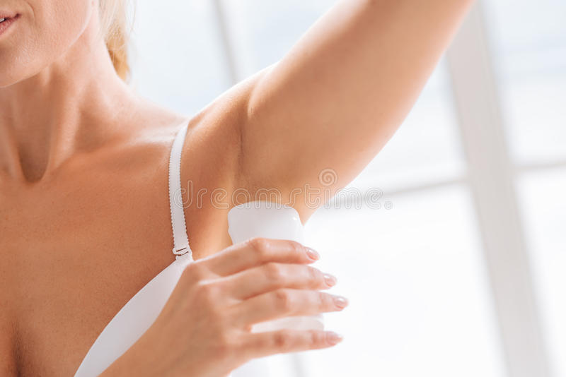 Закройте вверх женской руки ту держа ручку дезодоранта стоковые фотографии rf