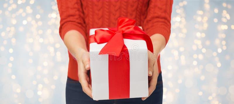 Закройте вверх женщины в красном свитере держа подарочную коробку стоковые изображения