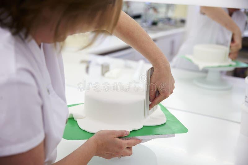 Закройте вверх женщины в хлебопекарне украшая торт с королевской замороженностью стоковые изображения rf