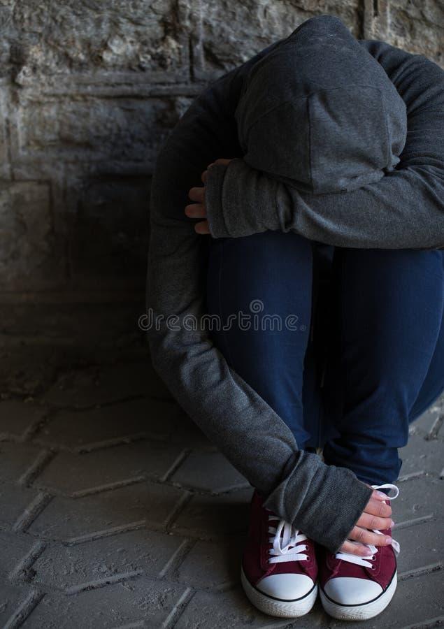 Закройте вверх женщины наркомана пряча ее сторону на улице стоковое фото