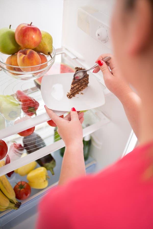 Закройте вверх женщины на диете крадя часть шоколадного торта стоковое фото rf