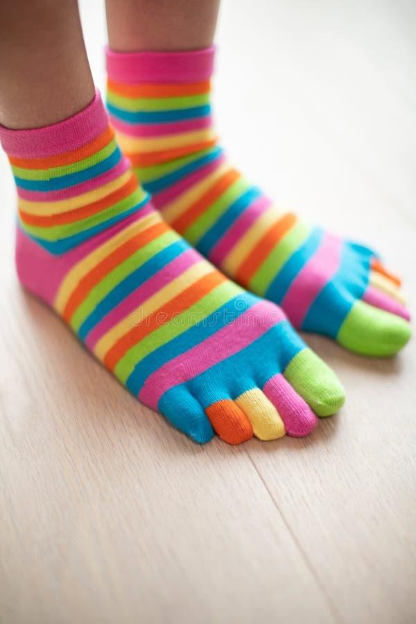 Закройте вверх женщины нося ярко покрашенные носки на ногах стоя на деревянном поле стоковое изображение