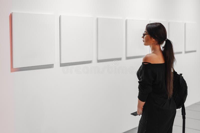 Закройте вверх женщины смотря пустые плакаты холста на стене в художественной галерее стоковое изображение