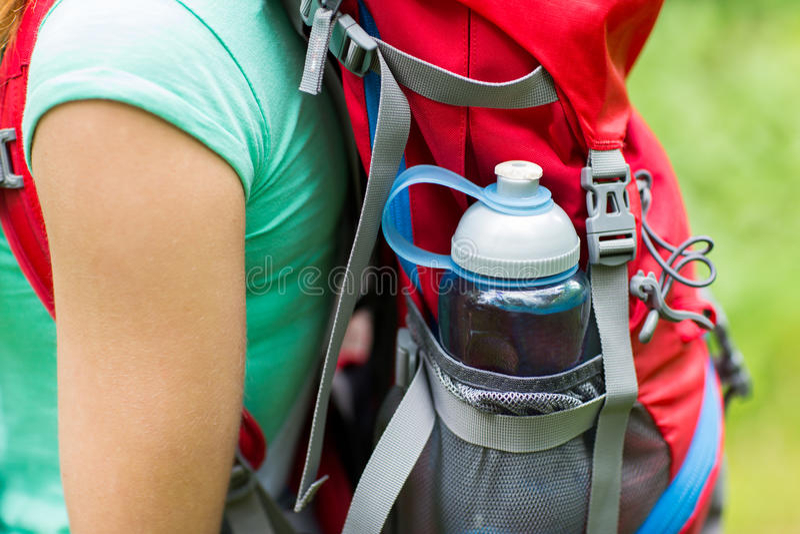 Закройте вверх женщины с бутылкой с водой в рюкзаке стоковое фото rf