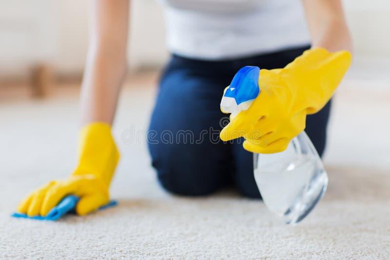 Закройте вверх женщины с ковром чистки ткани стоковые фото