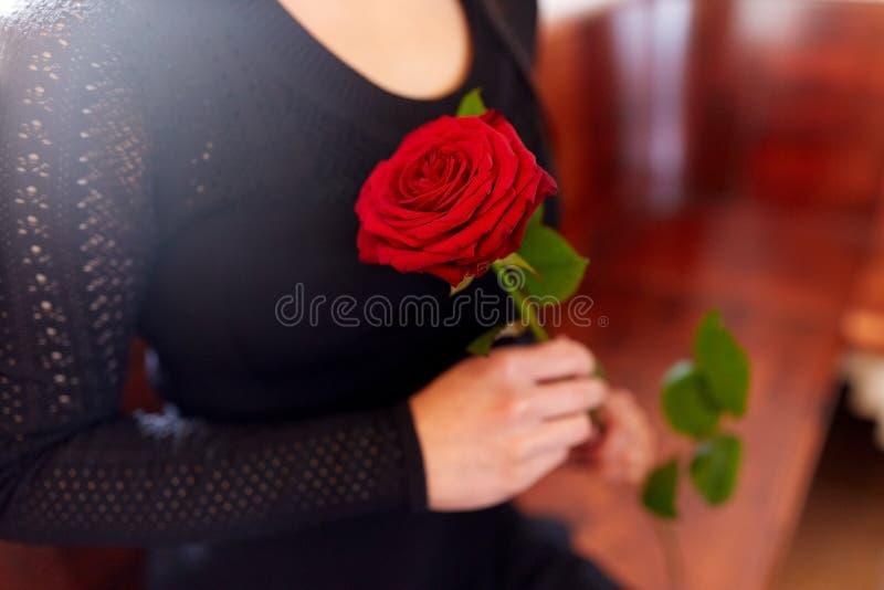 Закройте вверх женщины с розами на похоронах в церков стоковое изображение rf