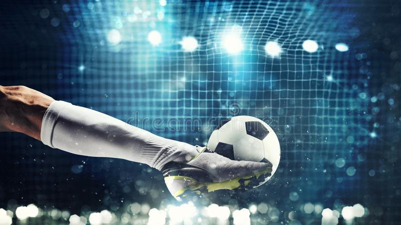 Закройте вверх забастовщика футбола готового к пинкам шарик в цели футбола стоковые изображения rf