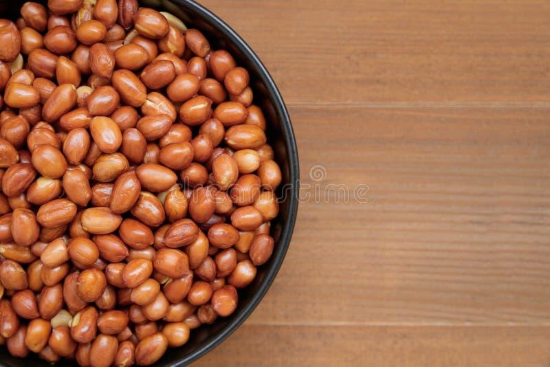 Закройте вверх зажаренных в духовке арахисов в черном шаре стоковые изображения rf