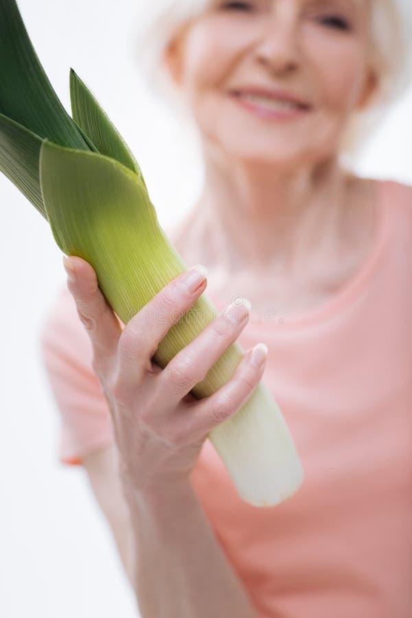 Закройте вверх зеленого лук-порея лежа в женской руке стоковые изображения