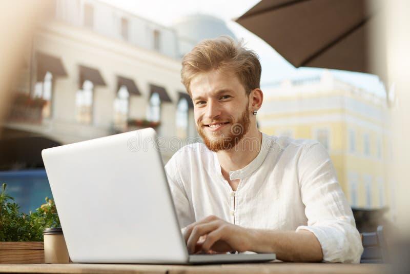 Закройте вверх зрелого побритого парня redhead в вскользь ультрамодных одеждах работая удаленно вне кафа, усмехаясь и смотря внут стоковые изображения