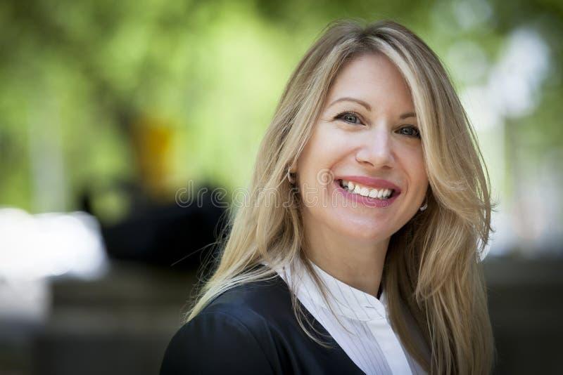 Закройте вверх зрелой счастливой белокурой женщины усмехаясь на камере thirties стоковое фото
