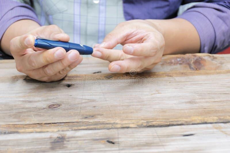 Закройте вверх используя lancelet на пальце к проверке уровня сахара в крови метром глюкозы стоковые изображения rf