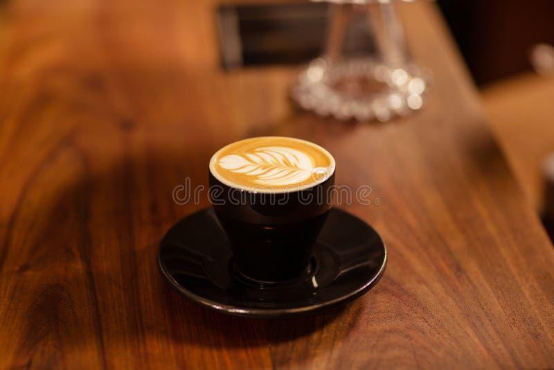Закройте вверх капучино с искусством кофе стоковые изображения