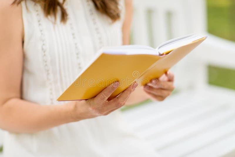 Закройте вверх книги чтения молодой женщины на парке стоковые изображения