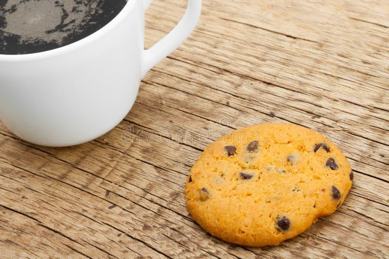 Закройте вверх кофейной чашки и печенья на старом деревенском деревянном столе стоковое изображение rf
