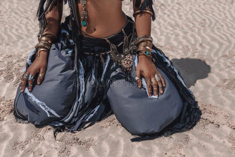 Закройте вверх красивого молодого стильного племенного танцора в восточном костюме сидя на песке outdoors стоковая фотография rf