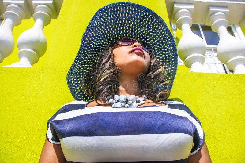 Закройте вверх красивой африканской женщины в голубом и белом striped платье моделируя перед традиционным домом bo-Kaap с lim стоковое фото rf