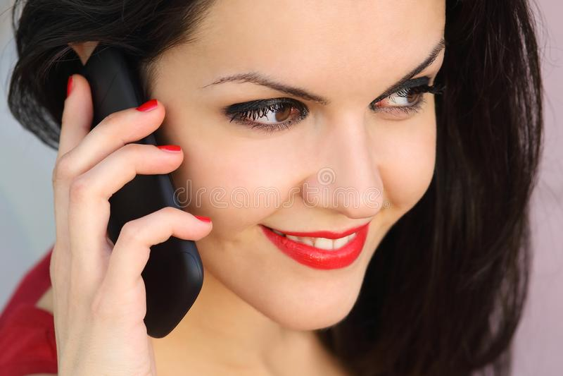 Закройте вверх красивой женщины на телефоне стоковое изображение rf
