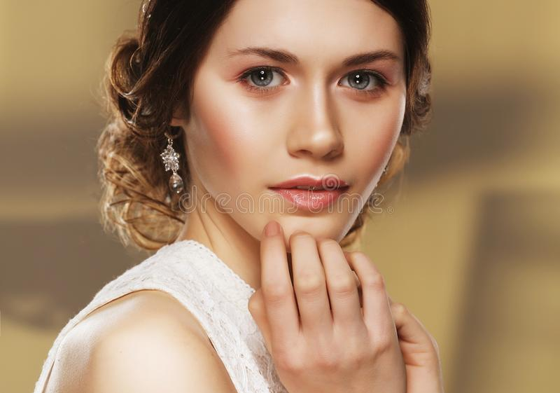 Закройте вверх красивой женщины нося сияющие серьги диаманта стоковые изображения