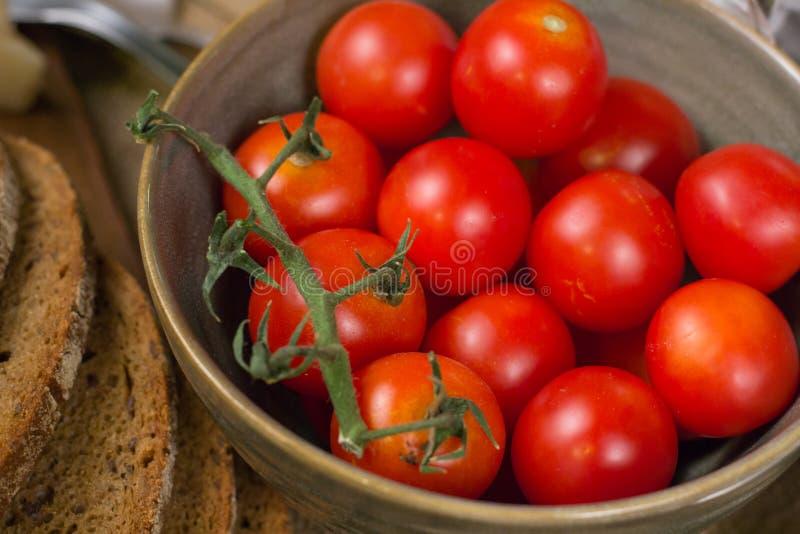 Закройте вверх красных томатов в зеленом шаре и кусках хлеба стоковые фотографии rf