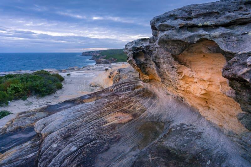 Закройте вверх красочной оранжевой горной породы с видом на океан ont его предпосылка стоковая фотография rf