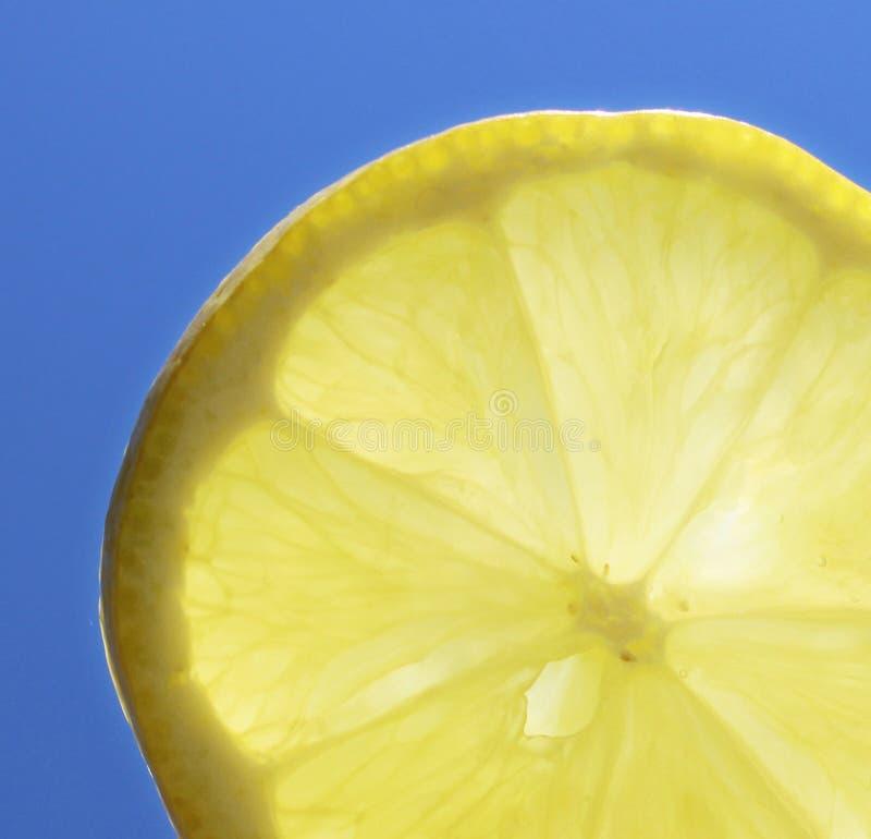 Закройте вверх кусок лимона лета солнечный перед сияющим солнцем и голубым небом в летнем времени стоковое фото rf