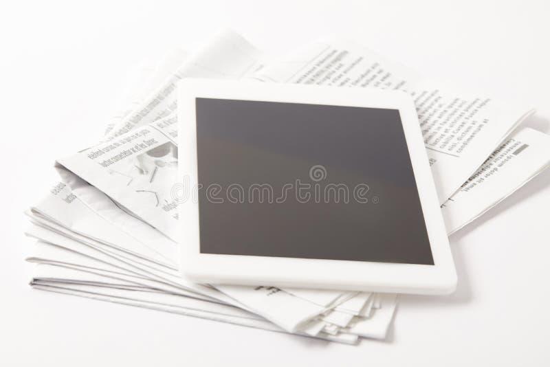 закройте вверх кучи газет с цифровой таблеткой, на белизне стоковое фото rf