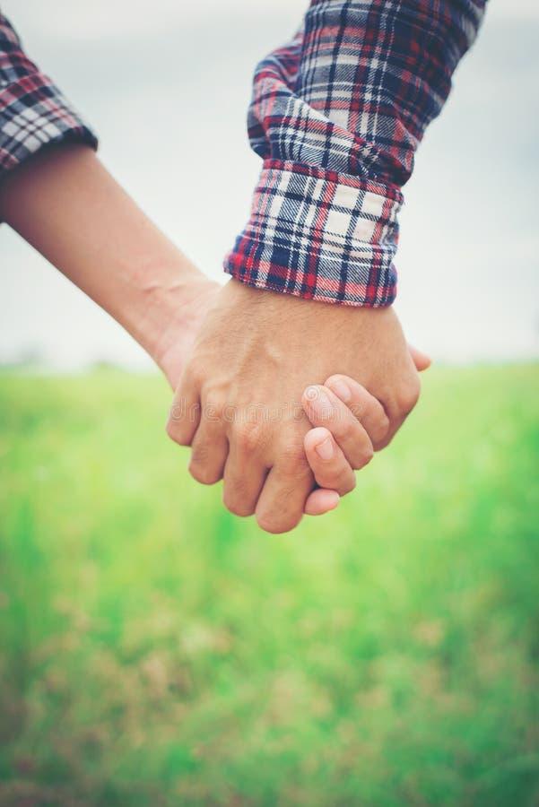 Закройте вверх любящих пар битника держа руки пока идущ на стоковые изображения rf