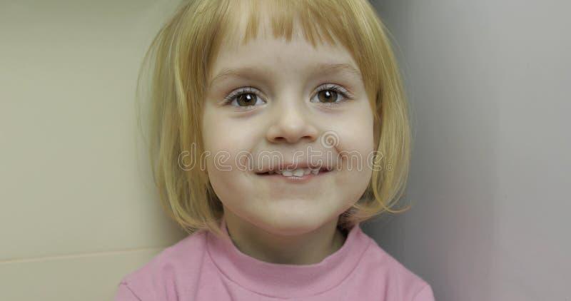 Закройте вверх маленькой белокурой милой стороны девушки Усмехаться девушки Внутрь E стоковое изображение rf
