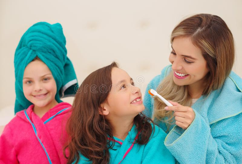 Закройте вверх мамы чистя ее зубы щеткой дочери в bathroom стоковое фото rf