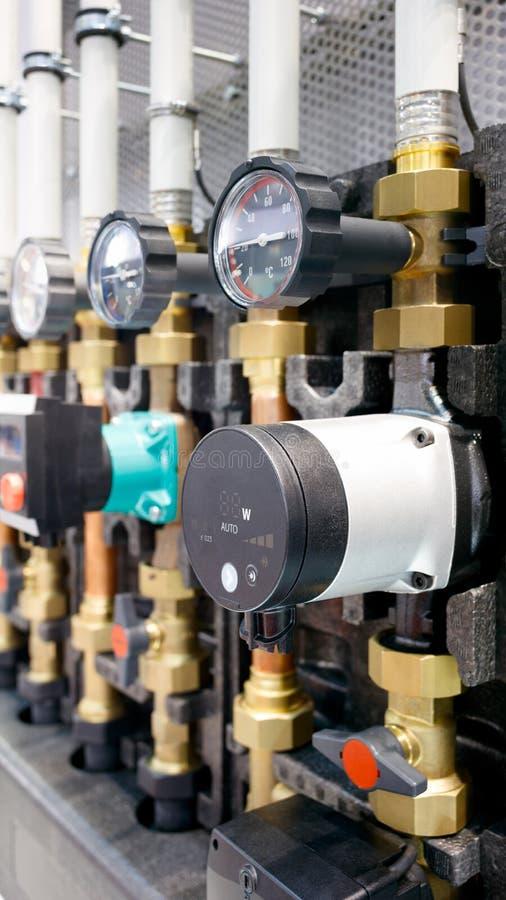 Закройте вверх манометра, трубы, измерителя прокачки, водяных помп и клапанов системы отопления в котельной стоковые изображения rf