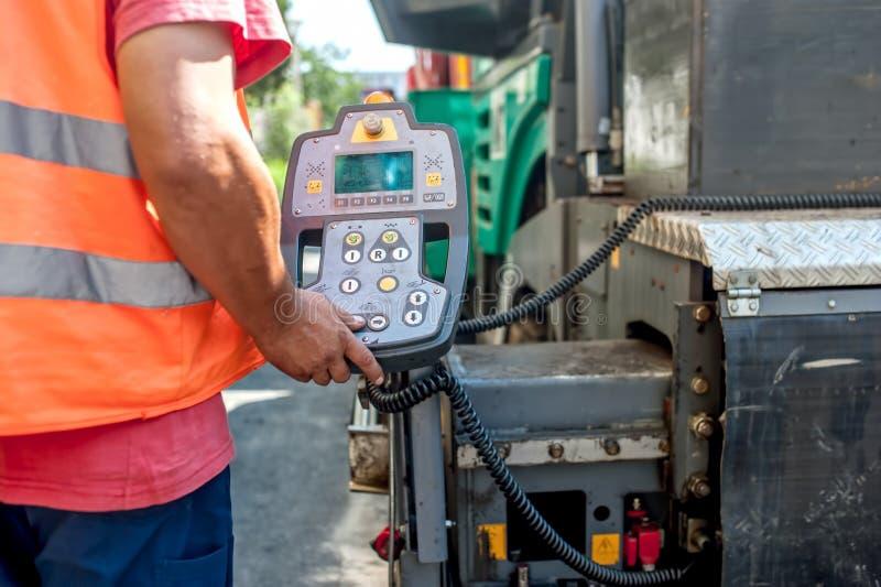 Закройте вверх машинного оборудования paver асфальта руки работника работая стоковые изображения rf