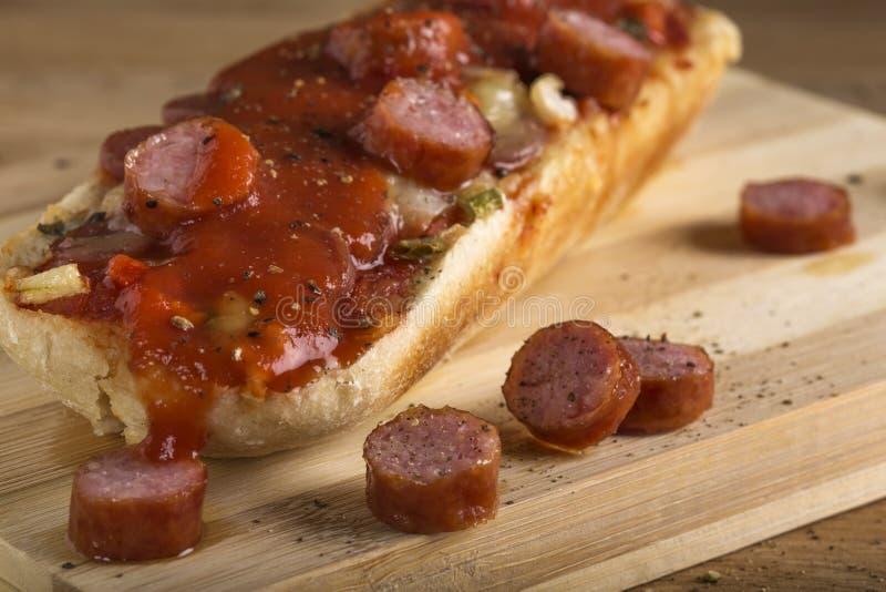 Закройте вверх мини пиццы с кусками sausagel на древесине стоковое фото rf