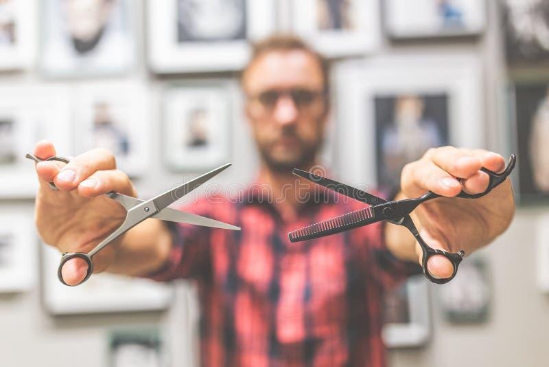 Закройте вверх модного парикмахера держа ножницы стоковое фото