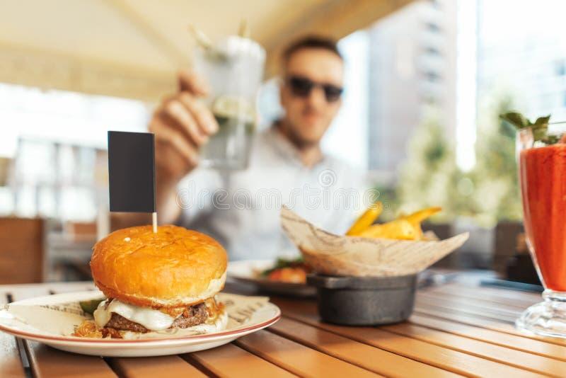 Закройте вверх молодого привлекательного человека держа стекло лимонада на кафе улицы стоковое изображение
