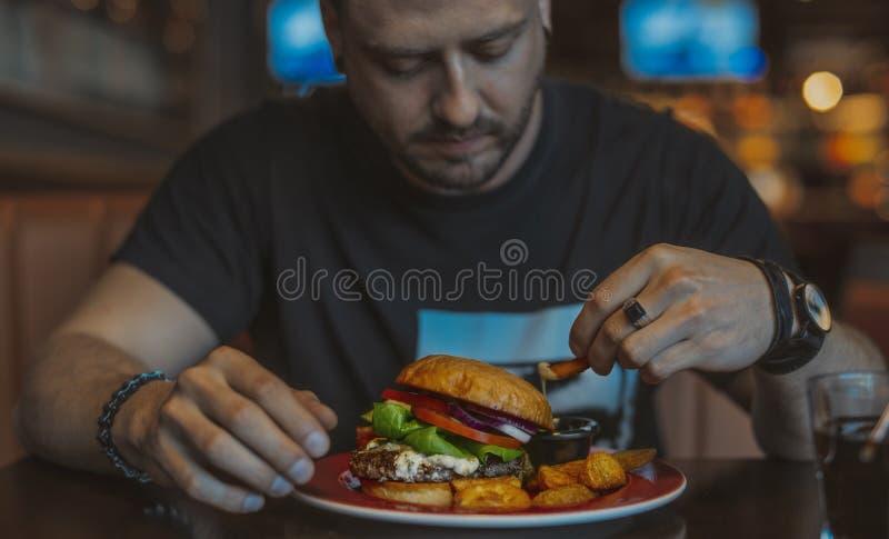 Закройте вверх молодого привлекательного человека есть фраи бургера и француза на кафе стоковые фото