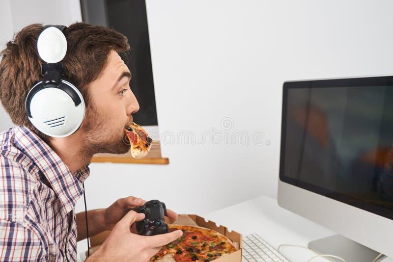 Закройте вверх молодого симпатичного небритого человека с короткими волосами в вскользь рубашке играя компютерные игры с регулято стоковое фото rf