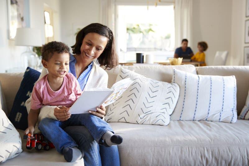 Закройте вверх молодой матери сидя на софе в живущей комнате с ее малышом на ее колене читая его книга, отец и сестра сидит стоковые фотографии rf