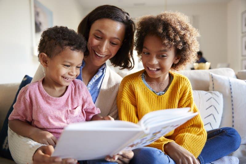 Закройте вверх молодой матери сидя на софе в живущей комнате с ее детьми, читающ их книга, низкий угол стоковое изображение