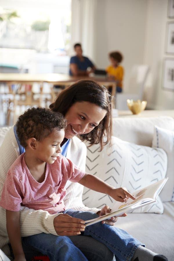 Закройте вверх молодой матери сидя на софе в живущей комнате читая книгу с ее сыном малыша, сидящ на ее колене, отец и стоковое изображение rf