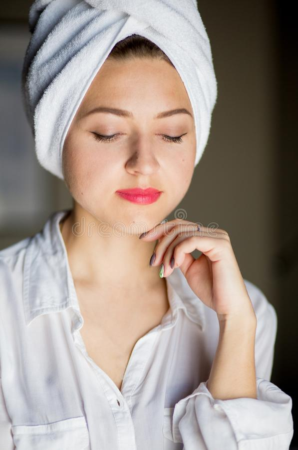 Закройте вверх молодой счастливой женщины после ливня с полотенцем на ее голове, с красными губами, касайтесь стороне и улыбкам стоковое фото rf