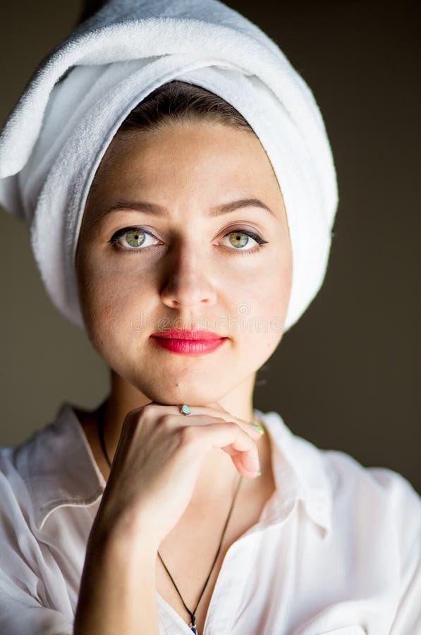 Закройте вверх молодой счастливой женщины после ливня с полотенцем на ее голове, с красными губами, касайтесь стороне и улыбкам стоковое изображение
