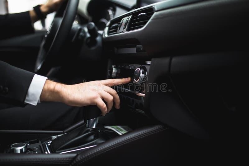 Закройте вверх молодого человека в костюме управляя автомобилем и переключая некоторую кнопку на панели автомобиля стоковое изображение