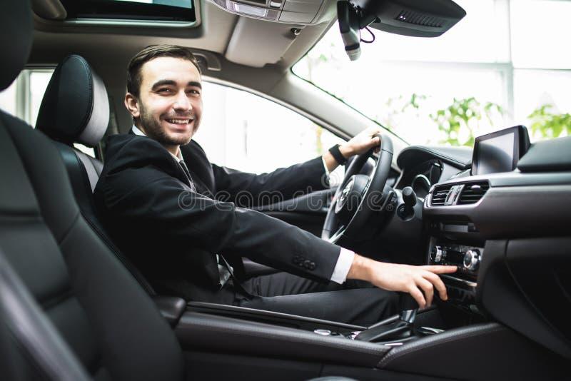 Закройте вверх молодого человека в костюме управляя автомобилем и переключая некоторую кнопку на панели автомобиля стоковая фотография rf