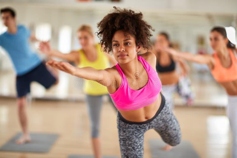 Закройте вверх молодой женщины на протягивать тренировку крытую стоковое фото rf