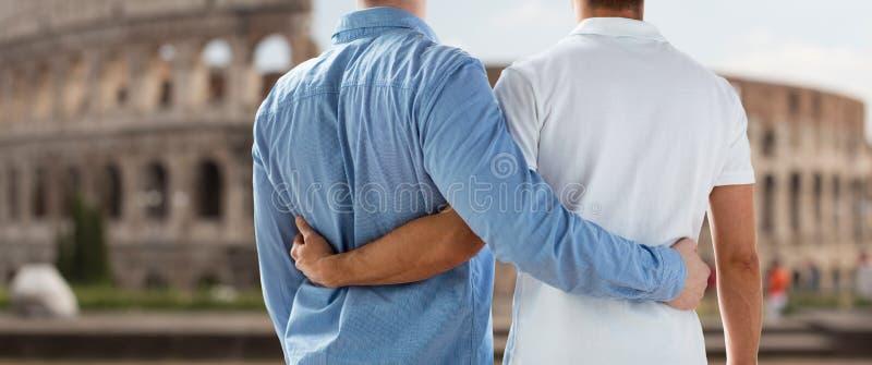 Закройте вверх мужских пар гомосексуалиста над Колизеем в Риме стоковое фото rf