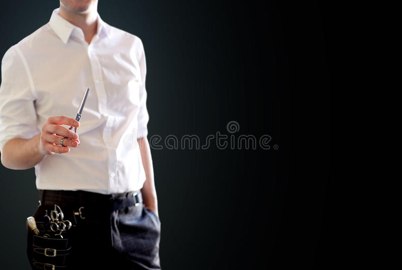 Закройте вверх мужского стилизатора с ножницами над чернотой стоковые фотографии rf