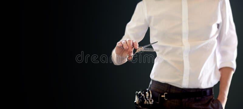 Закройте вверх мужского стилизатора с ножницами над чернотой стоковые фото