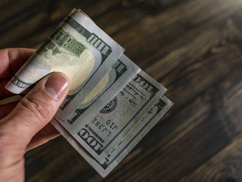 Закройте вверх мужской руки держит 2 банкноты 100 долларов на деревянной предпосылке новые счеты 100-доллара Доллар США денег стоковое изображение rf